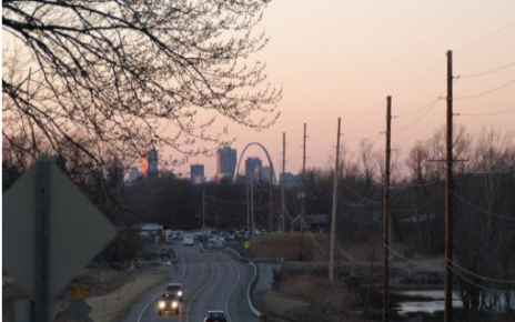 Image shows a city street with the STL Arch in the background